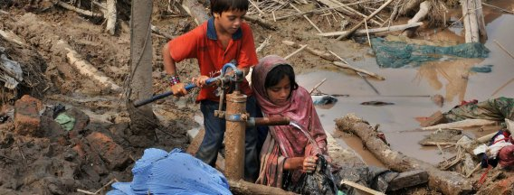 Two children using clean water pump in flooded area