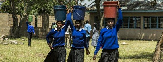 Tanzanian schoolgirls carrying water buckets on their head