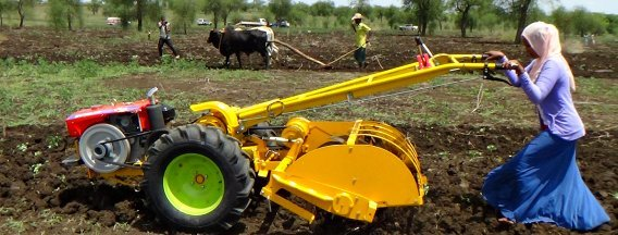 Woman handling agricultural machine in a field