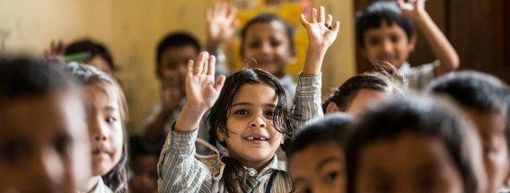 children raising hands classroom