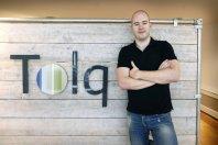 Entrepreneur beside logo on wooden wall