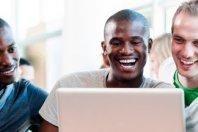 Laughing young men behind laptop