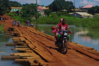 Motorcycle over wooden bridge in Guinea.